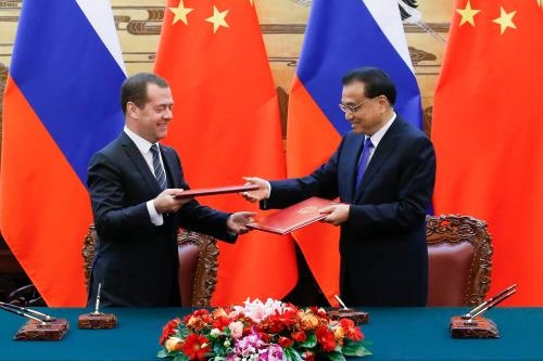 chinas xi russias medvedev stress improved relations